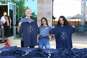 San Diego Christian College students holding up SDCC t-shirts for sale