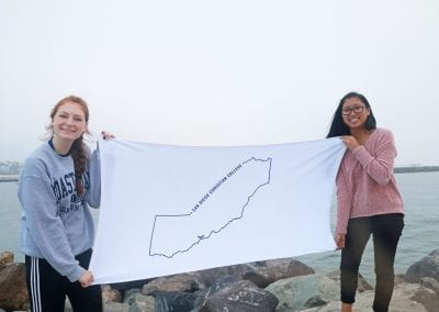 San Diego Christian College students pose beside the seashore with a map of California