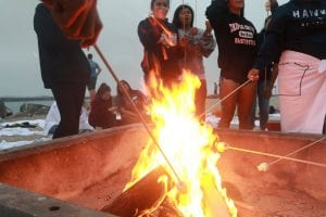 San Diego Christian College students roast marshmallows in a campfire on the beach