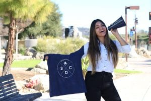 San Diego Christian College Cheerleader holding bullhorn and SDCC t-shirt