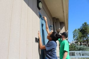 San Diego Christian College resident apartments, student paint doorframe