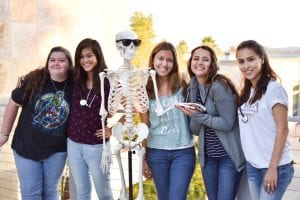 San Diego Bachelors of Biological Science pose with anatomy skeleton wearing sunglasses