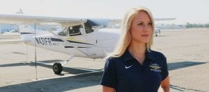 San Diego Christian College aviation student stands on runway next to small plane