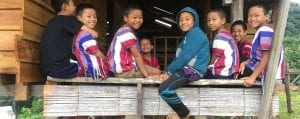 Global Missions smiling children pose while seated on small wooden wall